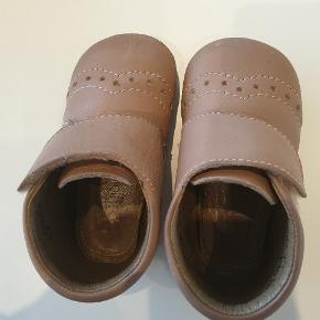 Brugt 1-1,5 md. Super sød sutsko til de små i lys pudderfarvet læder. Sutskoen har det klassiske hulmønster og lukkes let med bred velcrorem, så den er nem at komme i og justere. God fast hælkappe sikrer optimal støtte. Sutskoen har 2 gummifelter under skoen, som sikrer at dit barn ikke glider.  Smal til normal i bredden.