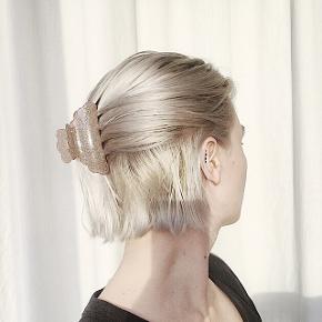 Glimmer hårklemme / hair claw i en fin pudret rosa/brun farve med glimmer. Har været brugt en enkelt gang - måler cirka 9cm og kan sagtens holde alt håret.   Kan sendes med dao igennem tradono-handel for 31.95kr (1-2 dage) eller postnord for 10kr (5 dage)