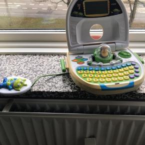 Toy Story Buzz Ligthyear computer V-tech Disney med  13 spil, rigtig god måde at lære tal, logik og bogstaver, sproget er dansk. Den er falmet i farverne og låget kan desværre ikke lukkes længere - kommer fra et ikke ryger hjem. Oprindelig pris var 750 kr. Sender gerne men på modtagers regning