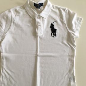 Hvid polo med sort hest fra Ralph Lauren. Har en super smuk og feminin pasform, og kan både bruges til hverdag og fest. Køber betaler fragt, hvis varen skal sendes.