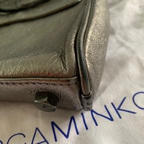 Åben for bud.   Rigtig lækker læder-crossbody fra Rebecca Minkoff. Tasken er sølvfarvet, og har også en lomme på ydersiden.  Der er mindre brugstegn på tasken, men ikke noget man lægger helt mærke til.   Der medfølger dustbag samt nye lædertropper/frynser til lynlåsene, som på billedet.   Tasken måler ca. L 25cm x H 17cm x B 5cm  Nypris omkring 1900,-
