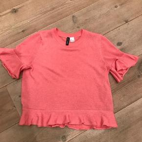 Varetype: T-shift Bluse i tynd glimmer strik med flæser Farve: Fersken Prisen angivet er inklusiv forsendelse.