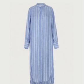 Blå/hvid stribet skjorte/kjole i viskose fra Munthe med stolpelukning, lange ærmer og bindebånd i halsen og ved ærmerne. Kjolen hedder Delicious og fås stadig i butikkerne.