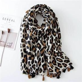 Nypris: 299,-  Smart lækkert blødt leopard tørklæde i leopard med frynser Det er dejlig blødt og meget behageligt at have på❤️❤️❤️  Materiale: Viskose, polyester og bomuld Mål: ca 90 x 180 cm Farve: Sort / brun / sand