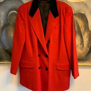 Vintage jakke fra 70'erne. Nyrenset.  Dobbeltradet og med sort velourkrave.  2 lommer. Knapper på ærmer.  Sort foer i polyester. Letvægter.  Uld og polyamid.  Mærke : First Lady.  Farven er postkasserød, men for rød til mig.