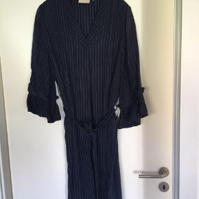 Smuk stribet kjole med bælte fra Karen by Simonsen - str 38. Længde ca 115 cm / bredde målt under ærme er ca 108 cm. Kjolen er lavet i et lækkert blødt materiale, den har v-hals, bælte og 3/4 ærmer. Jeg har brugt den både som alm kjole og som tunika ud over bukser. Brugt max 5 gange. Nypris 1199kr. Sender med dao / Mobilpay. Sender gerne for sælgers regning.