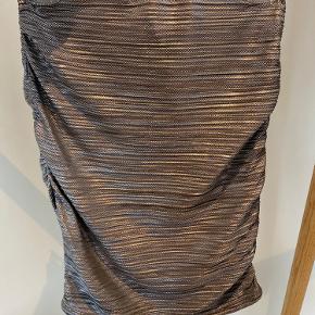 Nederdel fra Only i det fineste sølv / glitter materiale m.   Har en mellemhøj pasform, og har en fin rynke effekt i siderne, så gør at pasformen kan tilpasses.  Str. Xs