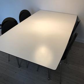 Hvidt spisebord med sort kant sælges.Bordet kan gøres længere med de to medfølgende tillægsplader. B: 100 L:170 (270 med tillægsplader) H:73 Der medfølger 6 stole til spisebordet. Bordet har en mindre skade i det ene hjørne (se billede).