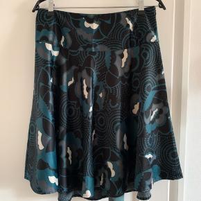 Lækker nederdel fra InWear sælges.  Let og luftig A-form, bredt bærestykke i livet og lynlås i siden. Indbygget underkjole.  82 cm i livet og 60 cm i længden.