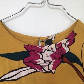Super fin bluse fra YAS i skøn gul farve med blomsterprint i bl.a. flaskegrøn og magenta. Blusen har korte ærmer, rund hals som lukkes i nakken med knap samt lille slids midtbag. Snittet er let boxy og kort. Str. S. 100% viskose. Kom med et bud. NP: 350kr.  Varen befinder sig i 9520 Skørping. Sender med DAO.  Se også min øvrige annoncer. Jeg sælger tøj, sko og accessories. Pt er min shop fuld af vintagekup, high street fund og mærkevarer i mange forskellige str. Kig forbi og spøg endelig!!