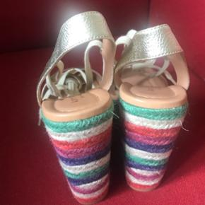 Superfede Kate Spade sandaler i guld og multi farvet. Ca.12 cm. hæl, men det er plateau, så de er fine nok at gå i:-) har kun været brugt få gange, og fremstår i næsten ny stand.Str.37,5 (nok mere en 37).