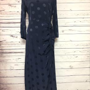 This Oliver Bonas long-sleeve, navy polka dot dress is inspired by multiple vintage dress trends. The chord can be adjusted based on how tight you want the bodice to hug your hips and how high you want the slit. Length of the dress is approximately mid-calf.  100% viscose.  Machine wash cold.