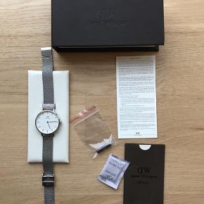 Flotteste Daniel Wellington ur sælges i sølv med hvid ur skive. Det sælges, da det ikke bliver brugt. Nypris er 1.195 kr. Urskiven måler 32 mm. Remmens bredde måler 14 mm.   Det er brugt så få gange, at det fremstår som ny. Der medfølger:  - Ur - Original æske - Papir fra Daniel Wellington  - Lille dut til at justere remmen.   Kan sendes på købers regning🌸