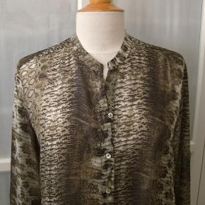 Bytter ikke!  Plus pakkeporto kr. 38,- uden omdeling, forsikret. DAO. Købspris kr. 1.600,-.   Super smuk skjorte, fra Sand, str. 42. Farve: brune men har et skær af vissengrøn, og cremet toner fra lys til mørkere. 100% Silke. Silken er naturlig letvægtsfiber med en glansfuld overflade. Skjorten er gennemknappet. Længere bagpå. Størrelsesguide str. 42: Bryst mål 94 - 97 cm Talje mål 76 - 79 cm Hofte mål 105 - 107 cm Længde fra nakken og ned 70 cm For og bag stykket målt ved bryst linjen, 112 cm. For og bag stykket målt ved hofte linjen 116 cm Kommer fra et ikke ryger hjem. Hænger i dragtpose