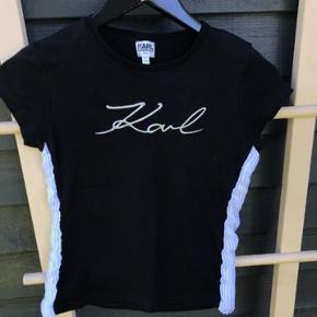 Sort t-shirt fra Karl Lagerfeld, med hvid plissé i siderne og sølv logo foran. Det er en str. 12 år, men en 10-11 årig ville også kunne passe den. Den er brugt få gange og i fin stand. Den er også i en rigtig god kvalitet.