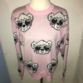 Lyserød tynd strik trøje fra det amerikanske mærke Joyrich. Med små teddy bjørne ansigter på i hvid. Størrelsen er en medium.