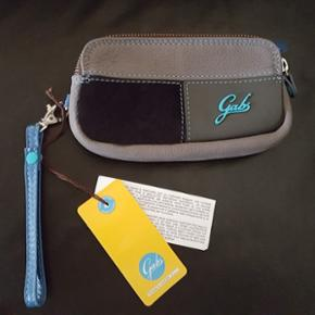 Brand: GABS Det italienske kvalitetsmærke GABS. Rigtig lækkert lille taske/pung i kalveskind med to separate rum. Er aldrig kommet i brug. Den sorte del foran er pels. Nypris 499kr.