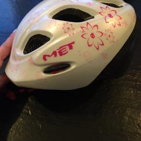 Cykelhjelm fra MET til de små str. 46-53 cm.  Hvid med pink blomster. God stand har ikke været i uheld.