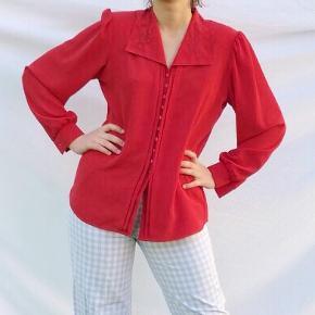 Rød skjorte med skulderpuder i str. 36. Brugt én gang og er så god som ny