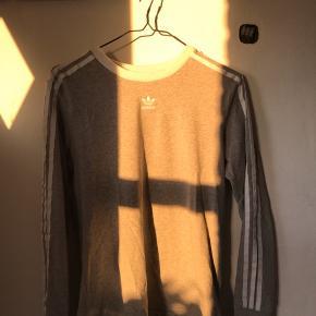Grå Adidas trøje med Adidas striber ned ad ærmet Sælges da jeg ikke får den brugt, BYD Kan sendes gratis