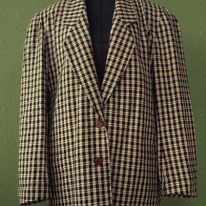 Blazerjakke formentlig fra danske Brandtex, fra 1980erne. Flot, enkeltradet blazerjakke med to udvendige, paspolerede lommer. Jakken er helforet.  Bundfarven er creme med tern i rødbrun og sort. Farven er svær at gengive, men se foto 2 for detaljer.  Materiale 55% uld, 43% polyester og 2% øvrige fibre.  Str. C40, passer en brystvidde på ca. 88-90 cm, en taljevidde på ca. 72-75 cm. Ryglængde ca. 73 cm.  Blazeren er ubrugt, fremstår ny, og opbevaret korrekt og røgfrit.  Kan sendes som MyPack Collect tracebar pakke med Postnord for 35 kr. (benytter ikke DAO).