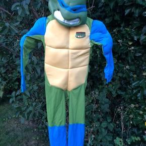 """Fin Teenage Mutant Ninja Turtles dragt med indlagte """"muskler"""" i armene. Har lidt skrammer og krads, se billeder.  Med maske og skjold  Str. 116"""