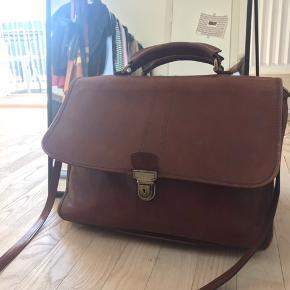 """Super lækker taske kan bruges  som skoletaske eller arbejdstaske, der kan sagtens være en Macbook 13 i og nogle bøger. Der medfølger en skulder rem.   Materiale: læder Mål: højde: 30 cm, længde: 36 cm bredde: 10 cm Rum: 2 """"åbne rum"""" i tasken, og 3 store rum med lynlås (1 inde i tasken, og 2 ude på.   Der er en smule patina, og spændet er lidt ridset men ikke noget der gør tasken grimmere efter min mening! Hvis billeder ønskes så send en PB!"""