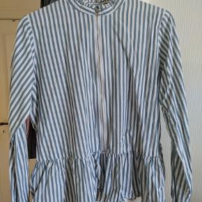 Blå/hvid-stribet skjorte med peplum og en fin detalje i halsen. Der er en lyn som kan lynes næsten hele vejen ned, hvilket gør den meget amme-venlig. 100 bomuld