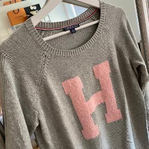 Virkelig skøn Tommy Hilfiger strik / trøje / sweater i grå farve med stort T i lyserød i en str. XL / X-Large / 42. Hvis man er til et oversize fit,  passes den af flere størrelser (mindre selvfølgelig).   Nypris 1200 kr. Købt i USA og var en limited edition. Den er brugt max 4-5 gange. Kan bestemt ikke ses.  Da jeg står og skal flytte og ikke har plads til hele min garderobe (😬), sælger jeg billigt ud af mit tøj. Prisen er derfor sat lavt. Tøjet fejler intet, med mindre andet selvfølgelig er beskrevet, og det er oftest som nyt, fordi jeg har været slem til at lave fejlkøb, så gør et kup ;-)  Der tages ikke flere billeder end dem, der er på annoncen, og hvis der ikke er billeder af tøjet på, er det, fordi jeg ikke kan passe det, og der tages derfor ikke billeder med det på  :-)  Køber betaler porto og TS-gebyr ved TS-handel. MobilePay haves, hvis man ønsker at spare gebyret.