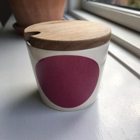 Lille lækker sukkerskål med trælåg og med plads til teske fra Helbak.  Skålen er råhvid / beige med en Rosa pink cirkel.  Ingen brugsspor Eller skår