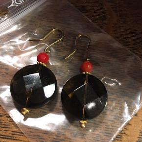 Øreringe, sorte facetteret perle og guldfarvet metal. Diameter på perle 1,7cm. Aldrig brugt. 50kr Kan hentes Kbh V eller sendes.
