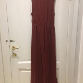Lang kjole i rustrød. Kjolen er en maxikjole. Den er uden ærmer og har et løst skørt.