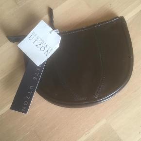 Varetype: Håndtaske/ clutch (NY) Størrelse: B 20 cm/ L 15 cm Farve: Sort  Lækker skind clutch /håndtaske i metallic foiled leather. Kraftig lynlås. Ligeledes indvendig lynlås lomme.  Har fået den i gave for et par år siden , får den ikke brugt. Der er stadigvæk skilte på.