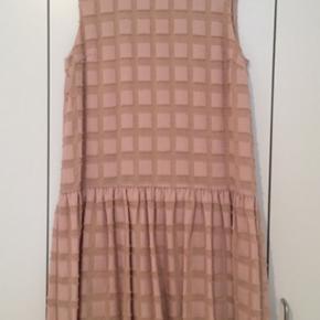 Kjole i støvet rosa i 42% viskose, 42% polyester og 16% polyamid. Den måler 55 cm.  Fra Skuldersøm ned til overskæring under taljen. Her måler den 50 cm. fra sidesøm til sidesøm. Brystmål lige ved ærmegabet er 45 cm. fra søm til søm. Vaskes på skånevask, Kjolen er aldrig brugt.