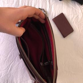 Fin og velholdt taske fra Adax Bordeaux rød med sølv detaljer God rumlig med flere små rum indvendig og et rum udvendig der lukkes med knap  Kommer med tilhørende kortholder