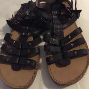 Cool Pom D'API sandal i sort læder med stjerne nitter. De er str 36. De er brugt få gange og fremstår i meget fin stand. Np var 699 min Mp er 225 pp og bytter ikke