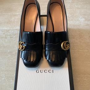 De fineste Gucci heels i sorte med logo sælges. De er købt i Gucci i Østergade i maj i år (nypris: 4500,-), men da de desværre var for små, er de kun blevet brugt 4 gange, og fremstår derfor som nye.  Der medfølger æsker og alle kort samt en pose med logo til hver sko. Skoene er egentlig størrelse 37.5, men jeg har sat dem til 38.5 her, da de er et nummer for store.