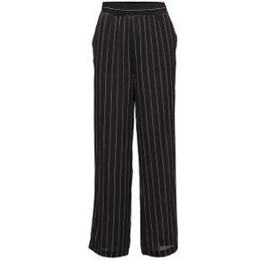 Sorte bukser med vidde og hvide nålestriber. Kvaliteten er let og lidt tynd. Bredt elastik foroven og lommer i siden.