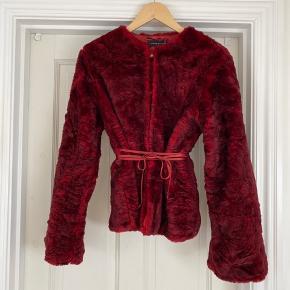 Smuk falsk pels med lækre detaljer. Kan også benyttes af en mindre størrelse grundet det flotte snit og bælte om taljen. Kan både bruges til fest og hverdag