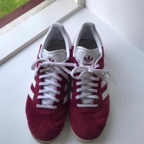 Sælger disse Adidas Gazelle Sneakers i Bordeaux/rød 🌟 str. 39.  De er ikke brugt meget og fremstår derfor i meget god stand. Skriv til mig, hvis du er interesseret!  Jeg mødes gerne, eller sender med Dao på købers regning!