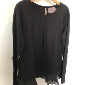 Sød bluse med chiffon peplumkant.  Lækker strækbar kvalitet. Lukkes med en knap i nakken.  Størrelsen hedder 158, men den svarer bedre til str 146/152.  65kr pp (DAO)