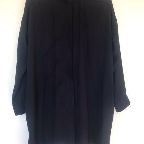 Smuk lang mørkeblå skjorte i rigtig fin stand. Materialet er meget fint og let. Farven er dyb mørkeblå.