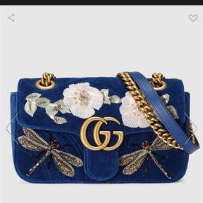 """Varetype: Håndtaske Størrelse: W22cm x H13cm x D6cm Farve: Blå Oprindelig købspris: 22225 kr.  Prisen angivet er inklusiv forsendelse.  Mødes også gerne.   Jeg sælger denne fine """"GG Marmont embroidered velvet mini bag"""". Den er aldrig blevet brugt og standen er derfor helt ny. Den har den smukkeste blå farve i velour, samt det fineste broderi.  Nyprisen var 22.225 kr og der følger dustbag og prisskilt med. Kvitteringen haves dog ikke. Jeg har været inde i Gucci i Kbh og har med hjælp fået en kopi af kvitteringen.   Flere billeder af tasken kan sagtens fremsendes."""