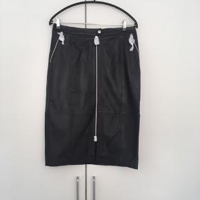 Lædernederdel med en lang lynlås foran og lommer med lynlås i begge sider.