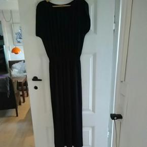 Lang sort kjole med elastik i livet. Kjolen falder utrolig flot. Kjolen er str. 36 og måler 140 cm fra nakke til bund.