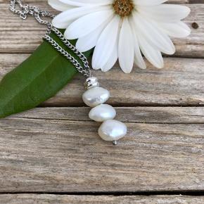 Halskæde med flot ferskvandsperler.  Perlen er natursten så den variere lidt fra gang til gang men ikke meget. Perlerne måler ca 9-10 mm i dia.  Kædens længde enten i 45 cm, 46 cm eller 50 cm Kæden er i stål så den forbliver flot og pæn og smitter ikke af.  Prisen er for både kæde og vedhæng  Kan sendes for 20,- med Post nord. Eller KUN 10,- som brev hvis man ikke ønsker smykkeæske med til kæden.