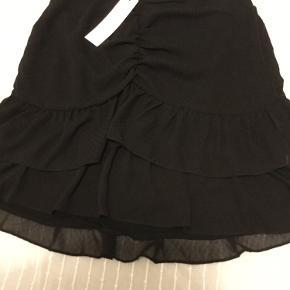 Suler fin kort sort nederdel fra Neo Noir str M, lynlås lukning bag på, rynke effekt og prik mønster i stoffet, har foer, ny med mærke nypris 399 kr.  Pris 150 kr + porto
