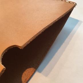 Brand: Kernelæder patina Varetype: Læder iPad/ tablet cover Størrelse: Ipad.  Kernelæder iPadcover.  Enkelt, stilrent, håndlavet og nordisk.  Coveret laves efter mål ved bestilling, og vi kan derfor tilbyde til alle typer iPad eller tablets.  Vi skal derfor vide hvilken type det er til, eller et stramt mål.  Disse laves i ældre kernelæder, derfor har de fra start en skøn patina og spor af forgangen tid.  Læder er et natur materiale, hvor ikke to stykker er ens og alt er håndlavet, derfor kan de variere i udtryk.  Pris 399kr  Kan afhentes i Aalborg, eller sendes med DAO