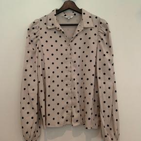 Lys skjorte med sorte prikker og pufærmer - shiny look; elastikkant v/ærmerne; fra ikkeryger hjem.