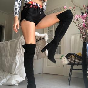 Super lækre knee high boots / thigh high boots / over knæet støvler med hæl. Har åben snip bag ved baglåret.  Sort imiteret ruskind. Hæl ca. 7-8 cm. høj. Brugt 1-2 gange, så i super pæn stand! Se billede 3 for eneste type af slid.